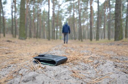 Young boy loses his purse with euro money bills on Russian autumn fir wood path. Carelessness and losing wallet concept