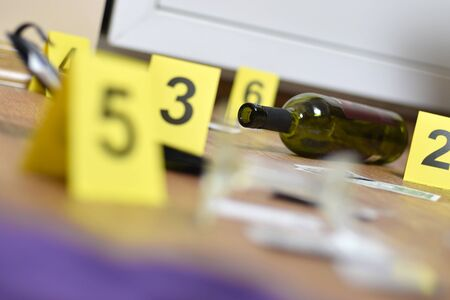Broken glass and bottle of wine marked as evidence during crime scene investigation. Many yellow markers with numbers close up Stock fotó