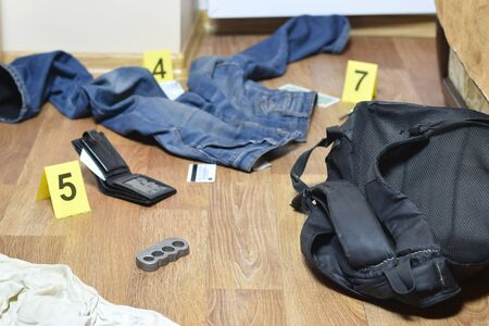 Crime scene investigation - numbering of evidences after the murdering in apartment. Brass knuckle, wallet and clothes with evidence markers close up Reklamní fotografie