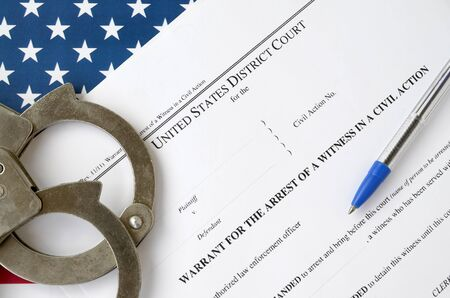 District court warrant for the arrest of a witness in a civil action papers with handcuffs and blue pen on United States flag. Concept of permission to witness arrest