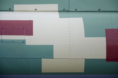 Side part texture of military helicopter painted in camouflage. Old armoured aircraft close up