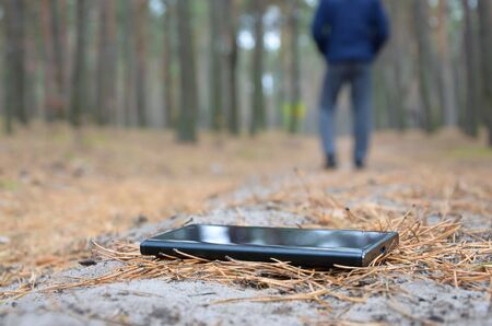 Young boy loses his smartphone on Russian autumn fir wood path. Carelessness and losing expensive mobile device concept 스톡 콘텐츠
