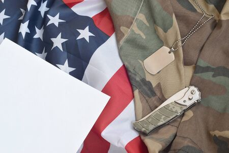 Army dog tag token and knife lies on Old Camouflage uniform and folded United States Flag. Background for Military day design