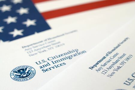 Envelopes with letter from USCIS on United States flag from Department of Homeland Security close up