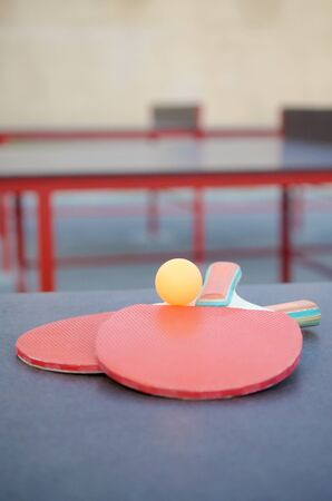 rackets and ball close up on table tennis table in outdoor sport yard. Active sports and physical training concept