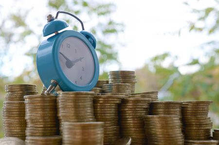 Blue alarm clock on big amount of shiny ukrainian old 1 hryvnia coin stacks close up on blurred green trees background. The concept of financial planning and business time management