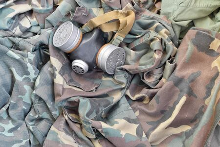 Stalker soldiers soviet gas mask lies on many green khaki camouflage jackets. Post apocalypse surviving concept Stock Photo