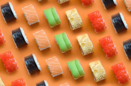 Different types of asian sushi rolls on orange background close up. Minimalism top view flat lay pattern with Japanese food