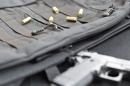 9mm bullets and pistol lie on a black tactical backpack. A set of special service items or a secret agent. Golden shells scattered around the handgun