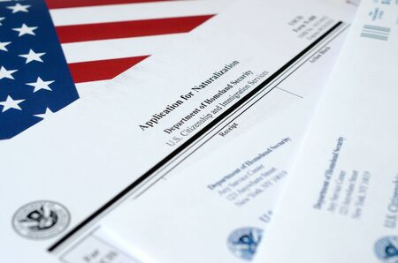 N-400 Application for Naturalization blank form lies on United States flag with envelope from Department of Homeland Security close up