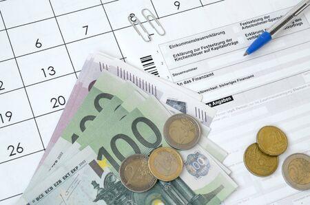 Il modulo fiscale tedesco con penna e banconote europee si trova sul calendario dell'ufficio. I contribuenti in Germania che utilizzano la valuta euro per pagare le tasse annuali