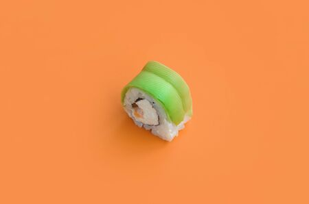 Vegetarian sushi roll with avocado and philadelphia cheese on orange background close up. Minimalism top view flat lay with Japanese food 스톡 콘텐츠