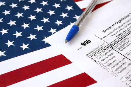 Form 990 Return of organization exempt from income tax and blue pen on United States flag. Internal revenue service tax form blank