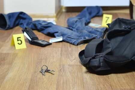 Crime scene investigation - numbering of evidences after the murder in the apartment. Keys, wallet and clothes with evidence markers close up