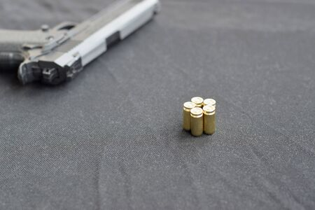 9mm bullets and pistol lie on a black fabric. A set shooting range items or a self-defense kit. Golden shells near handgun 스톡 콘텐츠