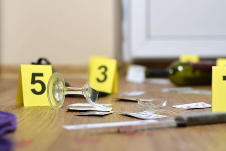 Crime scene investigation - numbering of evidences after the murder in the apartment. Broken glass of wine, knife and bottle as evidence close up Reklamní fotografie