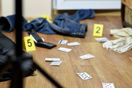 Crime scene investigation - numbering of evidences after the murder in the apartment. A lot of playing cards, wallet and clothes with evidence markers close up