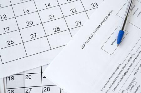 Visa application form to enter Japan and blue pen on paper calendar page close up