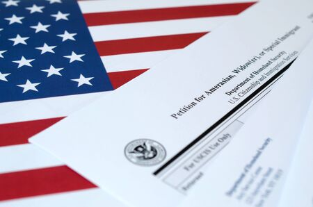 I-360 Petition for Amerasian, Widower or special immigrant blank form lies on United States flag with envelope from Department of Homeland Security close up