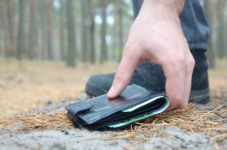 Male hand picking up a lost wallet from a ground in autumn fir wood path. The concept of finding a valuable thing and good luck
