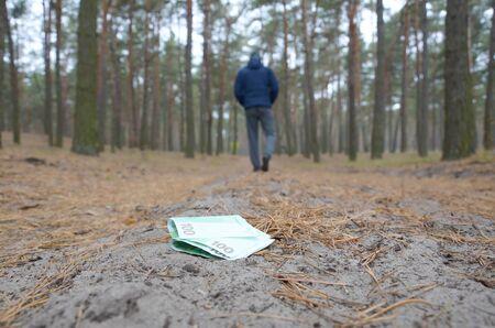 Junge verliert seine Euro-Geldscheine auf russischem Herbsttannenholzweg. Sorglosigkeit und Geldverlustkonzept Standard-Bild