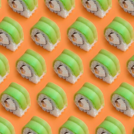 Vegetarian sushi rolls with avocado and philadelphia cheese on orange background close up. Minimalism top view flat lay pattern with Japanese food