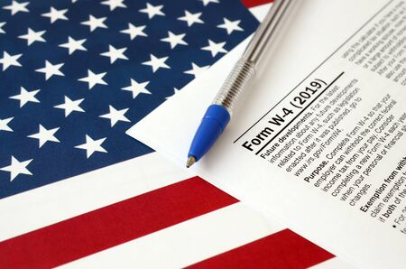 Form W-4 Employee's withholding allowance certificate instructions and blue pen on United States flag. Internal revenue service tax form blank