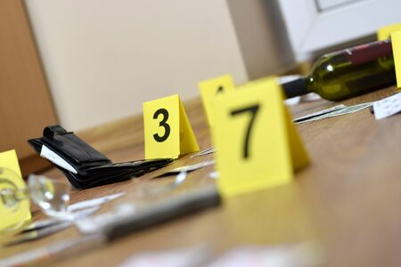 Crime scene investigation - numbering of evidences after the murder in the apartment. A lot of playing cards, wallet and bottle of wine as evidence close up Reklamní fotografie