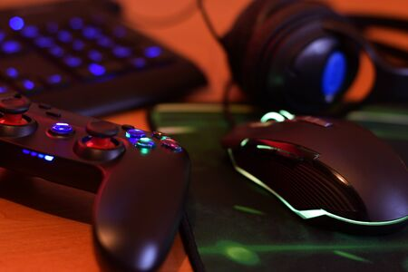 Modern gamepad and gaming mouse lies with keyboard and headphones on table in dark playroom scene close up. Cooperative teamplay concept Banco de Imagens