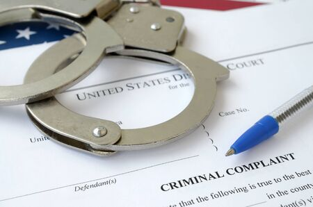 District Court Criminal complaint court papers with handcuffs and blue pen on United States flag close up Zdjęcie Seryjne