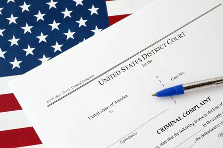 District Court Criminal complaint court papers and blue pen on United States flag close up