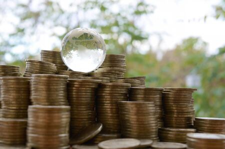 Glass planet on big pile of shiny ukrainian old 1 hryvnia coin stacks close up on blurred green trees background. The concept of money transfer around whole world. International banking concept