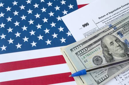 Form 990 Return of organization exempt from income tax and blue pen with dollar bills lies on United States flag. Internal revenue service tax form blank