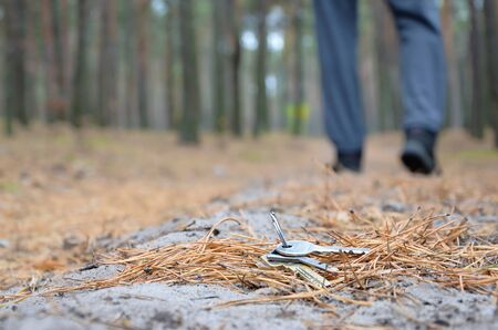 Young boy loses his keys bunch on Russian autumn fir wood path. Carelessness and losing keys concept