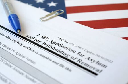 I-589 Application for asylum and for withholding of removal blank form lies on United States flag with blue pen from Department of Homeland Security close up