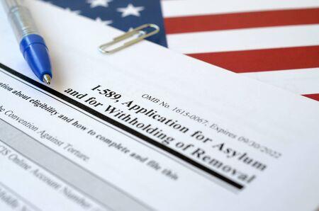 I-589 Solicitud de asilo y retención de expulsión, el formulario en blanco se encuentra en la bandera de los Estados Unidos con bolígrafo azul del Departamento de Seguridad Nacional de cerca