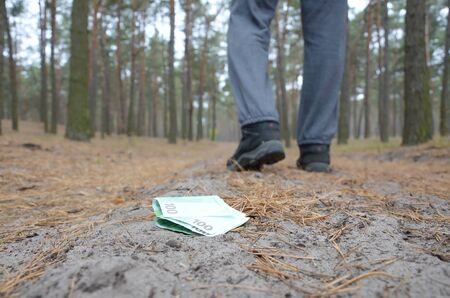 Young boy loses his euro money bills on Russian autumn fir wood path. Carelessness and losing money concept Banco de Imagens