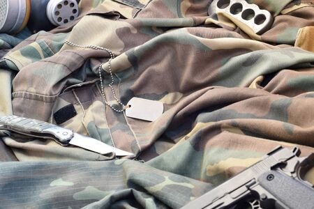 Stalker soldiers soviet gas mask lies with handgun and knife on green khaki camouflage jackets. Dog tags and brass knuckle. Post apocalypse surviving items kit Stock Photo