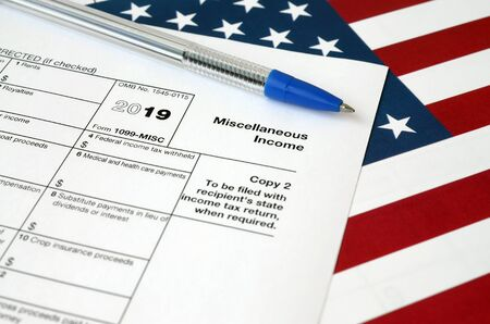 Form 1099-misc Miscellaneous income and blue pen on United States flag. Internal revenue service tax form blank Stock Photo