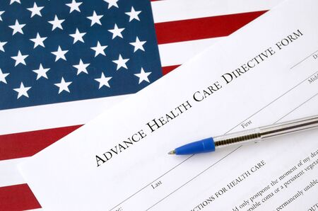 Advance health care directive blank form and blue pen on United States flag close up
