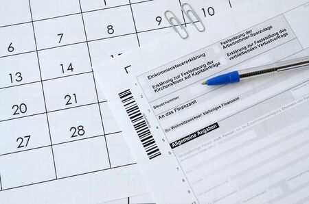 German tax form with pen lies on office calendar. Concept of annual tax paying in Germany