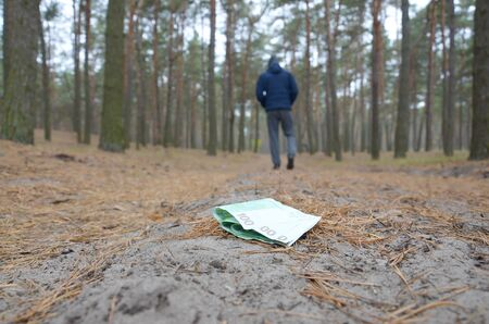 Young boy loses his euro money bills on Russian autumn fir wood path. Carelessness and losing money concept Zdjęcie Seryjne