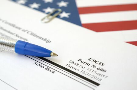 N-600 Application for Certificate of Citizenship blank form lies on United States flag with blue pen from Department of Homeland Security close up