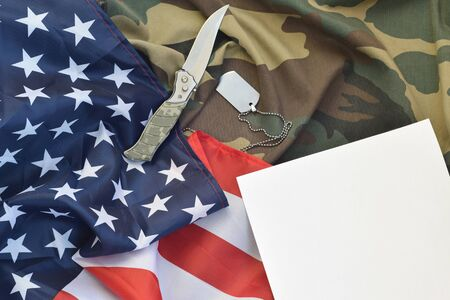 Blank paper lies with knife and army dog tag necklace on camouflage uniform and american flag. Space for notes or gratitude to US veterans day Stock fotó - 138343869