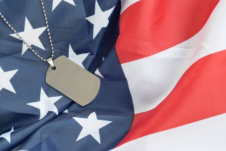 Silvery military beads with dog tag on United States fabric flag. Army token on USA banner close up. Veterans day concept