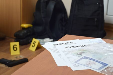 Evidence Labels and green card with ssn number lies on table with big amount of items as evidence in crime scene investigation process on background Reklamní fotografie