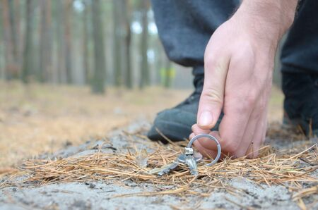 Male hand picking up a lost keys from a ground in autumn fir wood path. The concept of finding a valuable thing and good luck