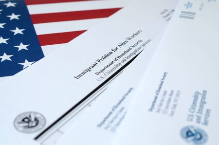 I-140 Immigrant petition for alien workers blank form lies on United States flag with envelope from Department of Homeland Security close up