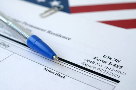 I-485 Application to register permanent residence or adjust status blank form lies on United States flag with blue pen from Department of Homeland Security close up