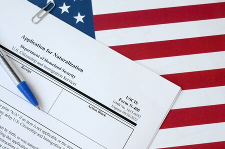 N-400 Application for Naturalization blank form lies on United States flag with blue pen from Department of Homeland Security close up